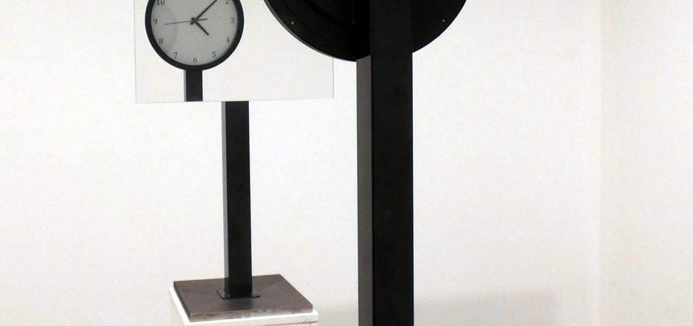 L'illusione del Tempo è un'opera che vuole indagare la complessità e l'impenetrabilità della lettura del Tempo. L'orologio in apparenza illeggibile dialoga con lo specchio, che riflettendolo lo rende leggibile: solo in un complesso rapporto di totalità i due elementi trovano ragion d'essere. Un banale orologio invertito getta dubbi sulla nostra concezione del Tempo: lo comprendiamo realmente? Secondi, minuti ed ore esistono nella realtà? Siamo sicuri degli strumenti utilizzati nella sua misurazione?