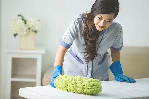 cleaner maid woman with duster and uniform cleaning table in living room at home.jpg