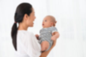 Copy-spaced image of an excited mother holding her son on hands over white.jpg
