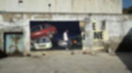 artiste zoer zoerism sebas velasco peinture acrylique sur mural d'epaves de voitures et sainer qui joue au foot en espagne