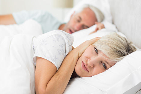 Woman having a restless sleep while her partner snores