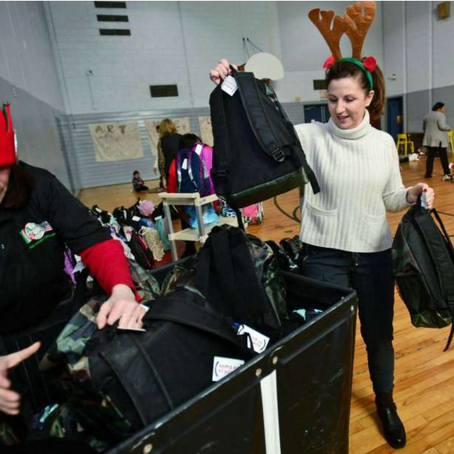 Volunteers with Filling in Blanks help deliver over 200 holiday backpacks