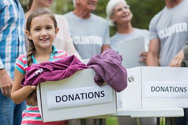 photo d'une enfants portant un carton sur lequel il est écrit donations