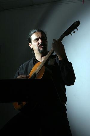 Kovács Gábor Muzsikus gitározik kotta előtt.