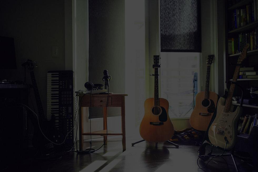 egy szoba látható hangszerekkel, gitárok, szintetizátor, mikrofon