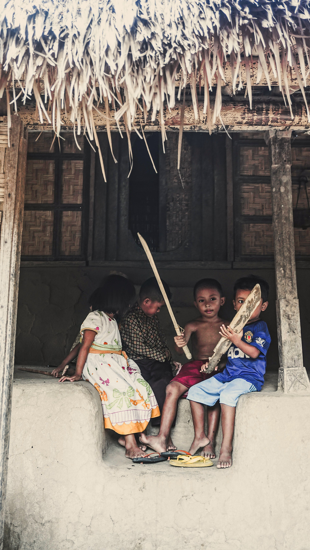 The children of Komodo village in Flores, Indonesia. Four small children playing together. Laba Laba Boat komodo tour.