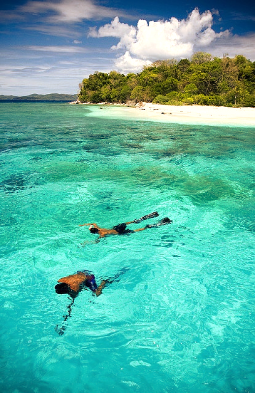 Young couple in honeymoon snorkle on uninhabited beach in Komodo Island. The island is called Bidadari, located in Flores, Indonesia. Perfect for Komodo diving trip and snorkel tip. The best boat in Labuan Bajo is Laba Laba Boat.