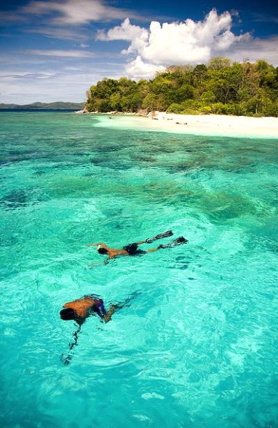 Bidadari island or angel island in Komodo. two guys swimming at beautiful beach in Bidadari Island resort. Komodo boat tour.