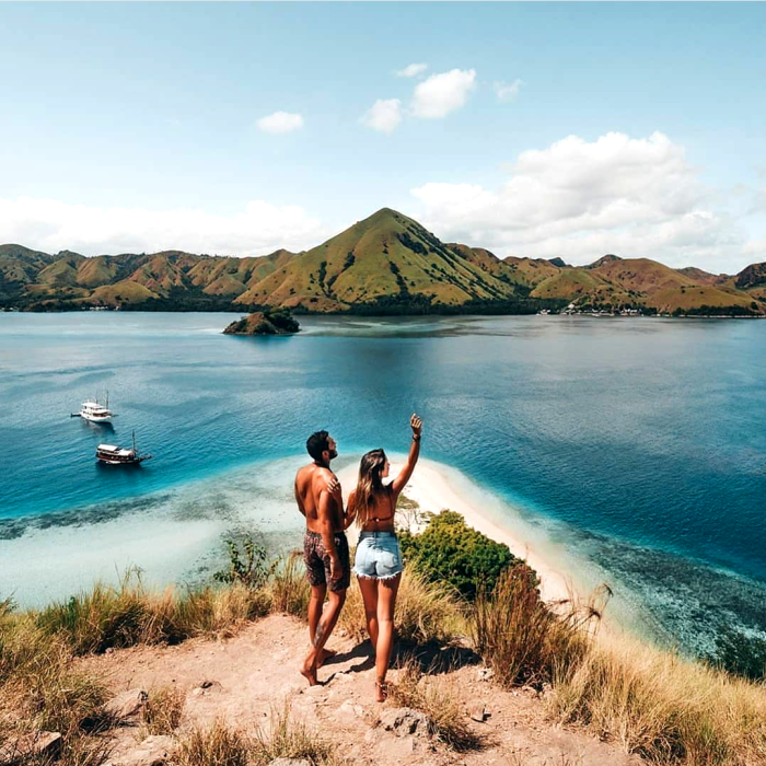 A couple hiking to the top of Kelor Island in Komodo. Beautiful small island located in Komodo. snorkle at Kelor island. Komodo island boat tour.