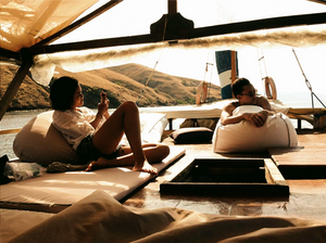 Private Komodo Island Liveaboard Tour with Laba Laba Boat. honemoon couple relaxing on top of a luxury yacht in Komodo island, enjoying sunset together. Summer luxury vacation to Komodo island with a boat. Laba Laba Boat.