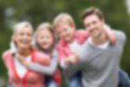 Parents Giving Children Piggybacks In Co