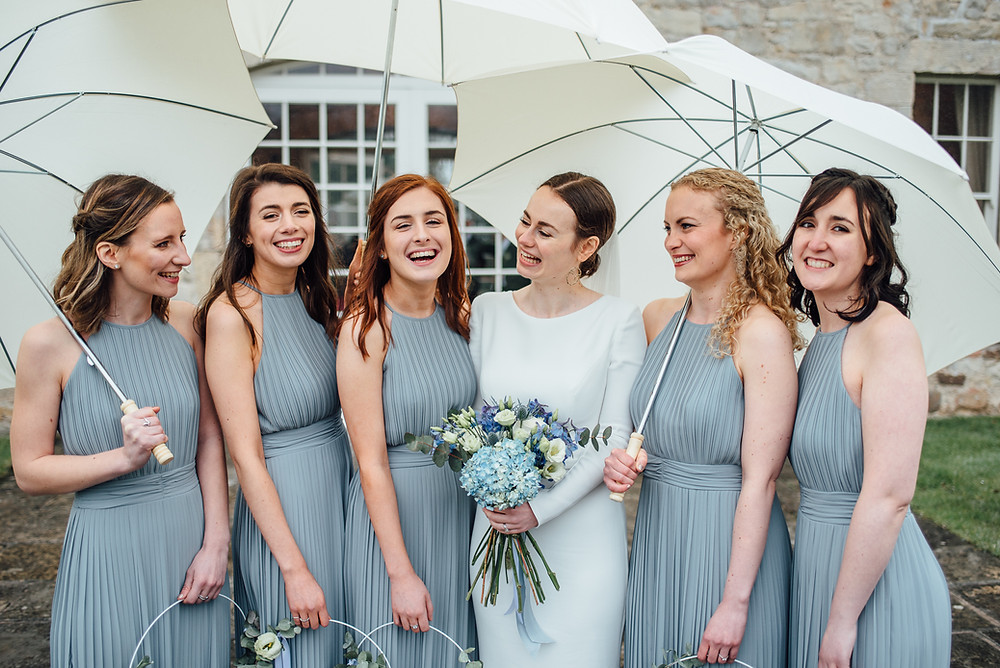 Rainy wedding bridal party photo outside Kirknewton Stables