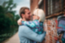 couple hugging in front of grafitti in urban engagement shoot