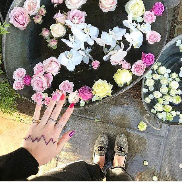Rosie Fortescue stands in chanel shoes with her hand out showing her nail art manicure by LG Nails London wearing Rosie Fortescue Jewellery
