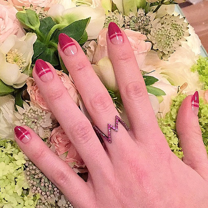 Rosie Fortescue has her hand against a bunch of flowers wearing a red negative space nail art manicure by LG Nails London and a ring from rosie fortescue jewellery