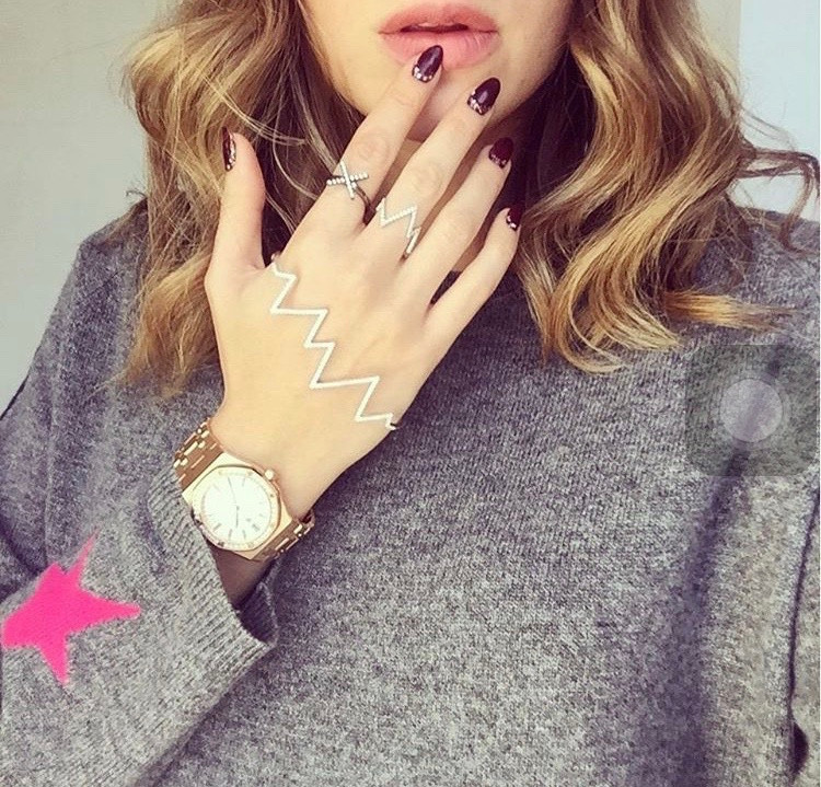 Rosie fortescue holds her hand against her lips to show her nails and rosie fortescue jewellery