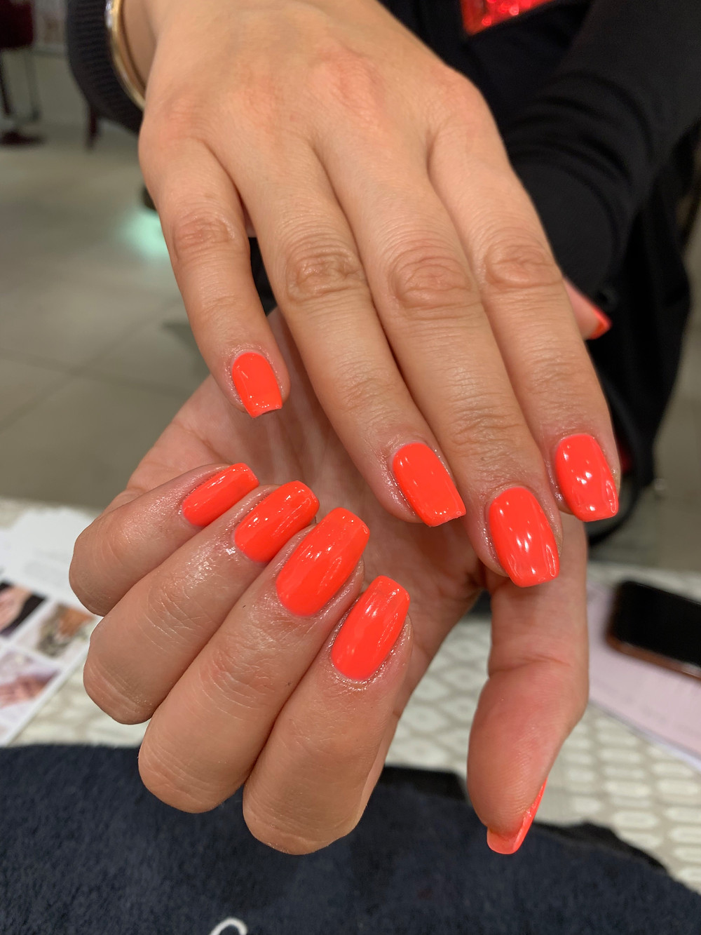 hand model shows neon orange manicure in Gelish i'm brighter than you