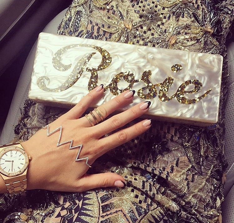 made in chelsea star, Rosie Fortescue hand models her jewellery and manicure against a clutch bag which reads 'Rosie'
