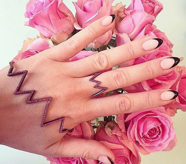 Rosie Fortescue has her hand against a bunch of pink roses wearing a black french tip nail art manicure by LG Nails London and a ring and cuff from rosie fortescue jewellery