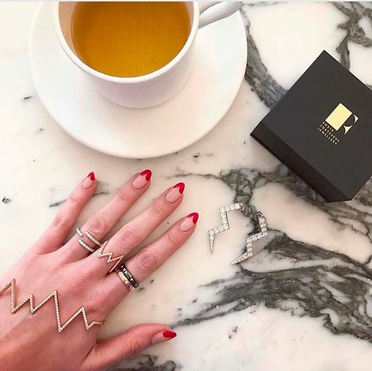 Rosie fortescue models her LG Nails London manicure on a marble table wearing rosie fortescue jewellery in london
