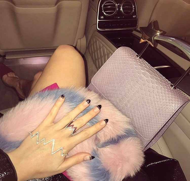Rosie Fortescue has her hand against her bag wearing a black negative space nail art manicure by LG Nails London and a ring and cuff from rosie fortescue jewellery