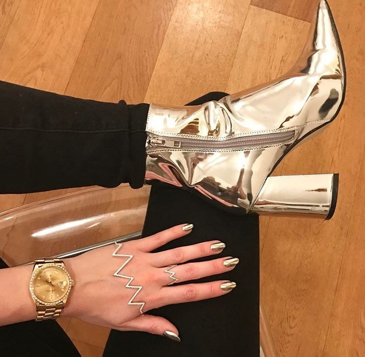 Rosie fortescue hand models her chrome nail art manicure by LG Nails London by putting her hand against her chrome boots