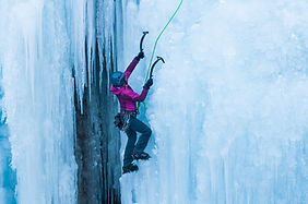 athletic woman in pink coat climbing ice