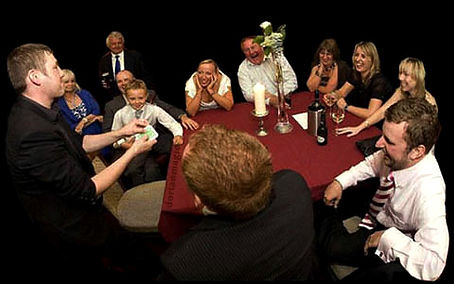 Dorian magician performing for guests at a table.