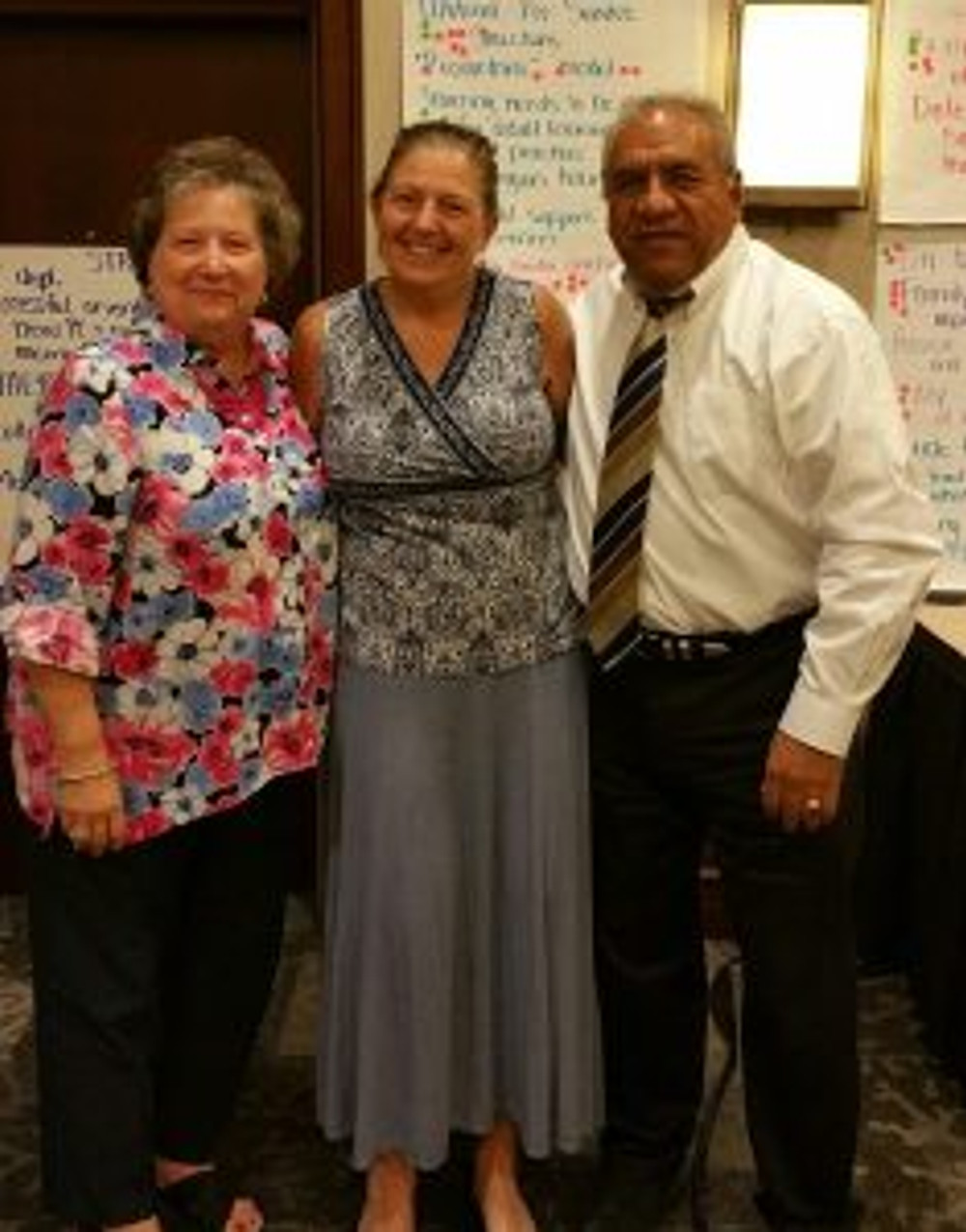 Preschool teacher Kerry Cormier stands with QA Manager Beth Zinkand and CEO Dr. Jose Villa.