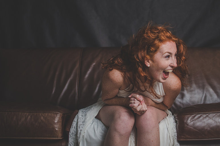 Redhead woman with freckles in a white dress smiling while sitting on a couch with her elbows on her knees