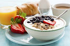 healthy breakfast array with bowl of oats and berries, strawberries, water, and croissant
