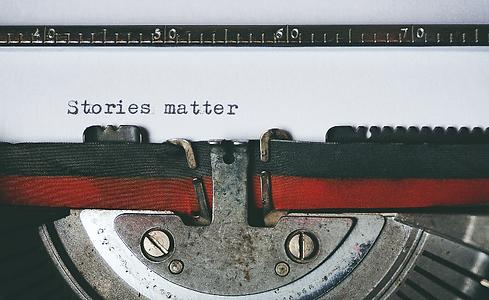 """Der Beginn eines Buchs: Schreibmaschine tippt """"Stories matter"""" auf ein weißes Blatt Papier."""