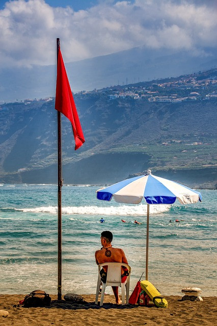 Lifeguard sitting in chair on the beach, parasol and flag pole