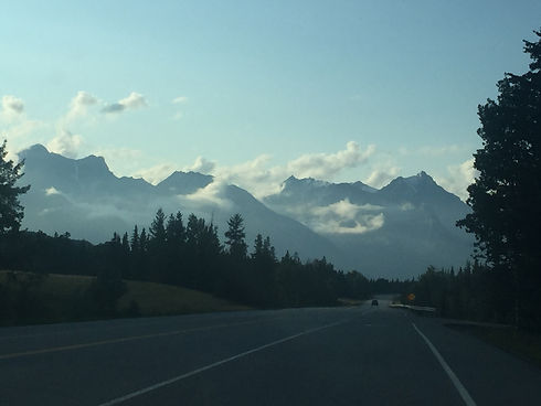 Photo of driving down a highway at dusk into the mountain valley. This a view you can see if you're driving through the mountains on the way to Golden Gaze B&B in Golden B.C.