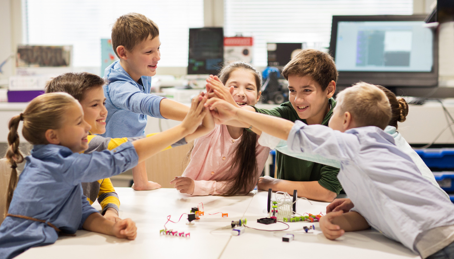 education, children, technology, science and people concept - group of happy kids building robots an