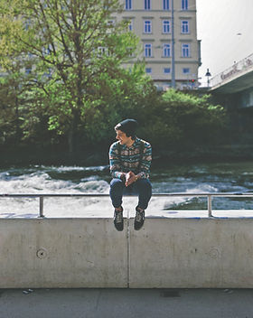Guy sitting on bridge