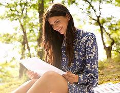 mujer-sonriente-en-el-bosque-leyendo-una