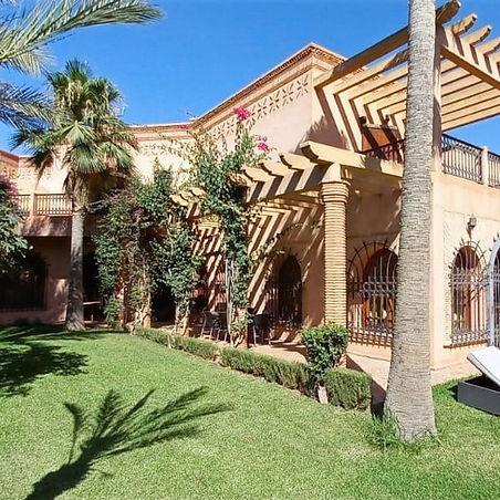 Magnifique villa à l'architecture classique de Marrakech avec piscine proposée à la vente au quartier Targa .  Construite sur un terrain arboré de 1200 m² environ et une surface habitable de 600 m² répartie sur 2 niveaux, la villa comprend un triple séjour avec de beaux espaces, une cuisine équipée, WC invités. A l'étage, vous trouverez une grande suite parentale avec terrasse comprenant un dressing et une salle de bain,  3 autres chambres avec salles de bains privatives et placards, terrasses. Une piscine d'environ 4x14 ml traitée au chlore et jardin arboré avec un arrosage automatique.  2 places abritées de stationnement, chauffage solaire. Notons que la villa a été construite il y a une vingtaine d'années et quelques travaux de remise au goût du jour sont à faire par les nouveaux propriétaires.
