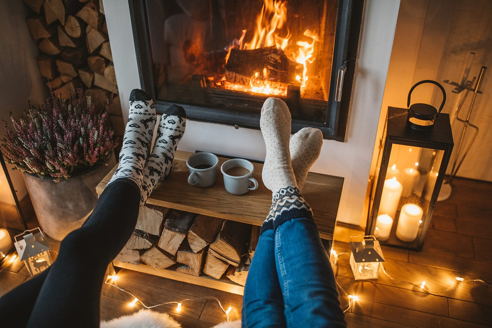 Two pairs of feet warming in front of a fire