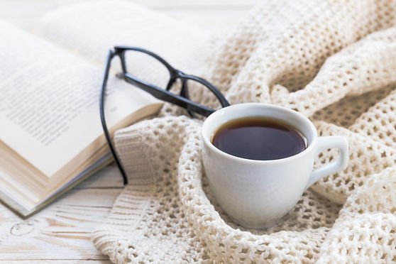 A cup of coffee on a blanket next to glasses