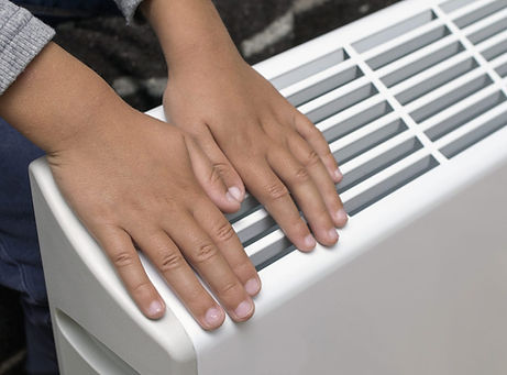 Two hands on an electric storage heater