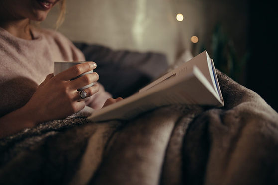 Woman reading a book with a cup of tea