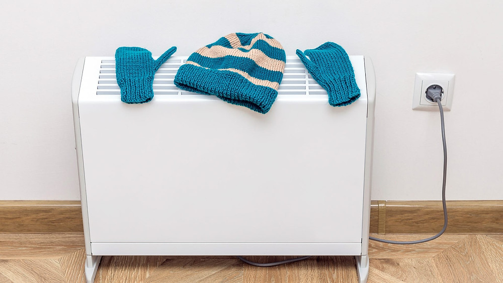 Woolly hat and gloves drying on a radiator