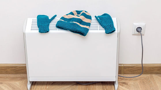 Woolly hat and gloves on electric storage heater