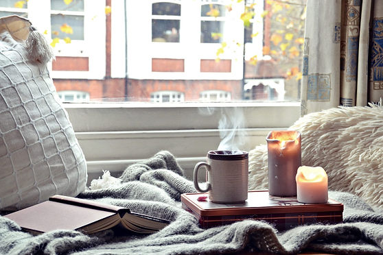 A hot cup of tea and candles next to a window