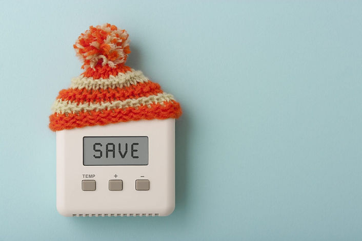 An electric heating control panel wearing a woolly hat