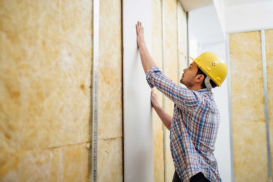 Construction worker putting up plasterboard