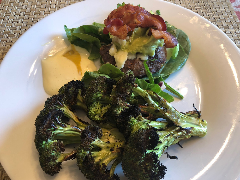 Broccoli, bacon, burger on a bed of lettuce on a white round plate with mayonnaise and mustard