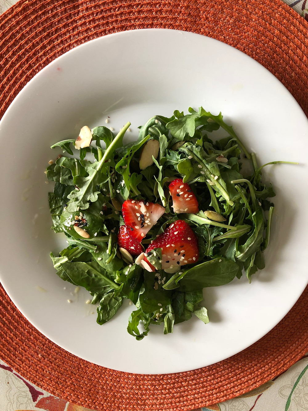 Salad with strawberries on plate of greens