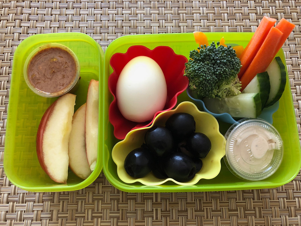 healthy kid lunch nutritious apple slices nut butter black olives egg ranch broccoli bell pepper carrots cucumber